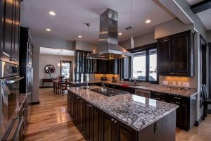 22-kitchen-with-dark-cabinets-and-white-wave-granite-countertops